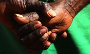 An Aboriginal elder stands with her hands behind her back