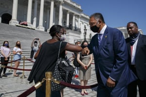 Tonya Jones, of New York City, left, bumps elbows with the Rev Jesse Jackson outside the Capitol on Tuesday.