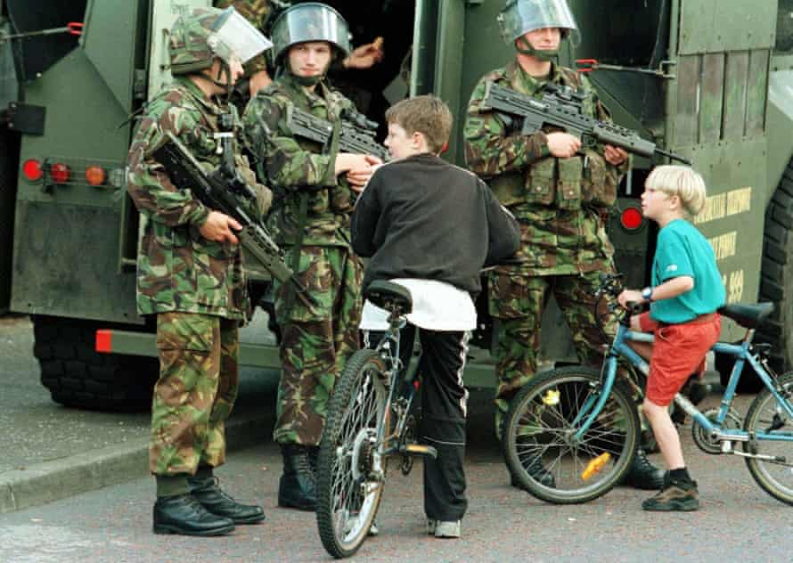 Young boys talk to British soldiers on the peace line in west Belfast, 1996
