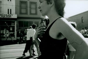Photograph of a woman drinking beer on the street.