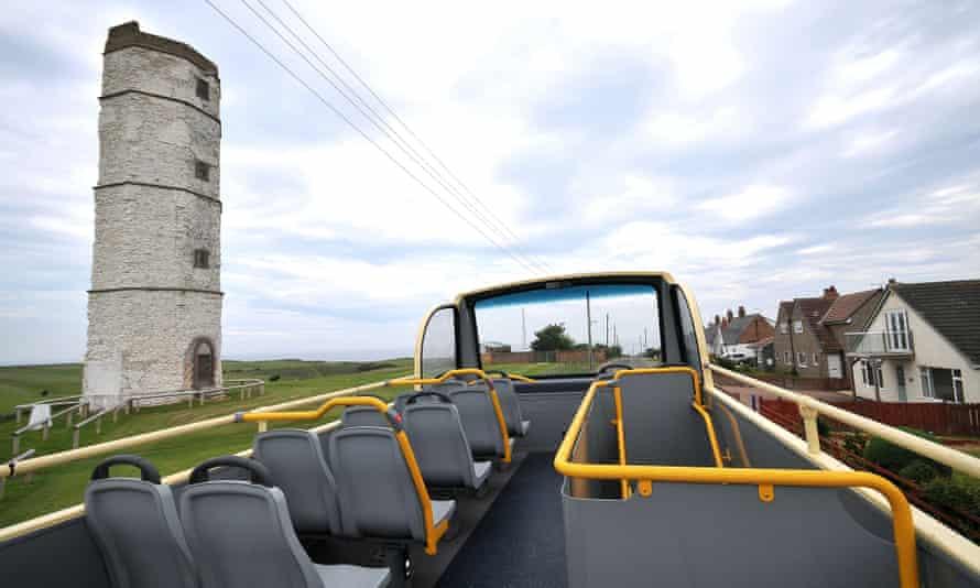 Bridlington Beachcomber bus passes the lighthouse near Flambrough Head, UK.
