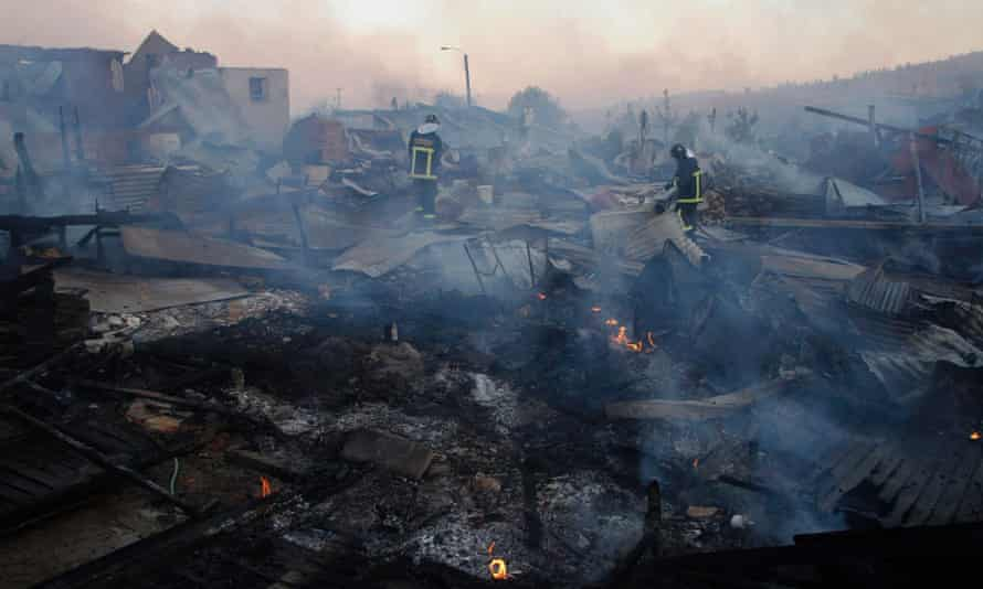 Firefighters working amid the remains of buildings destroyed by a fire in Cauquenes, Chile.