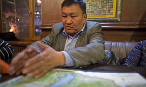 Tumursukh with a map of Mongolia's national parks sits in a cafe near the environment ministry in the Mongolian capital, Ulaanbaatar.