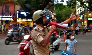 A police officer uses a loudspeaker to disperse people gathered in Bangalore as residents prepare for a week-long lockdown.