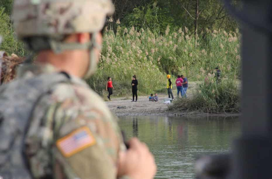 A soldier looks across the Rio Grande River from Laredo, Texas, into Nuevo Laredo, Mexico, where a group of people hang out on the river bank.