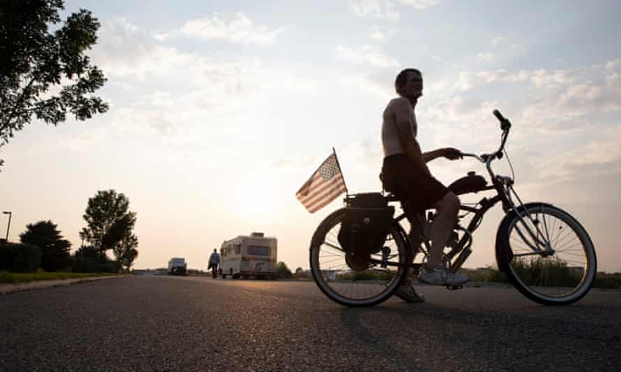 Michael Schmidt, an employee at IHOP restaurant for eight years, sits for a portrait on his bike on the street where he – and others – are living in their campers, in Bozeman, Montana.