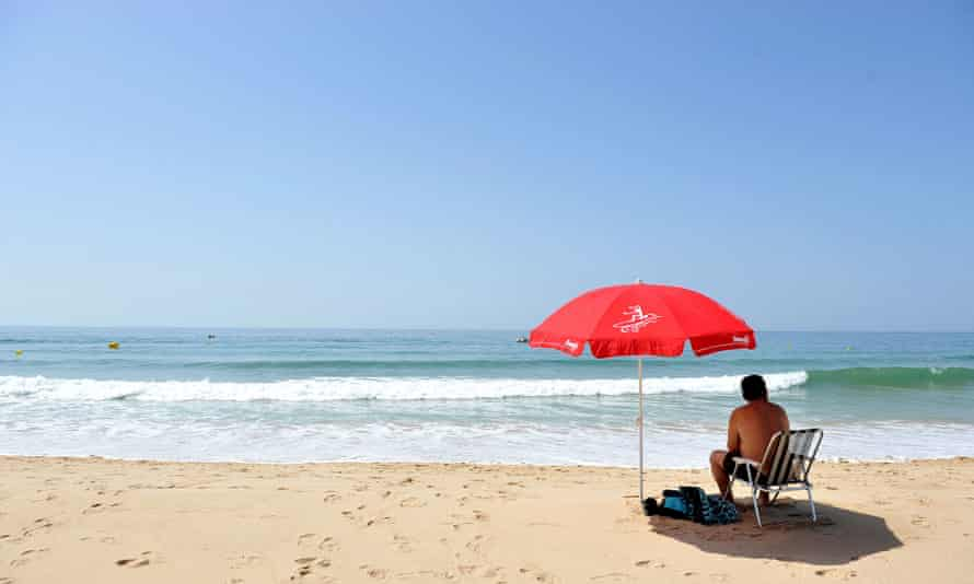 man sitting under an umbrella on a portuguese beach