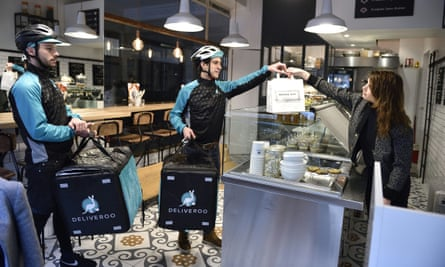 Deliveroo couriers picking up meals for delivery from a restaurant.