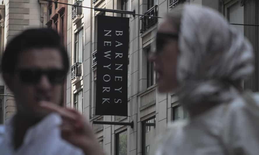 Pedestrians pass Barneys department store in New York