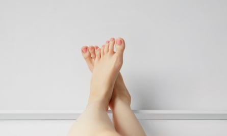 Foot over White Headboard in Bedroom. Close Up of Bare Feet in Bed at Home, Awaking Good Morning. Beautiful Woman Body Slim Legs and Pink Nail Polish Manicure Background, Sleep Relax Concept.