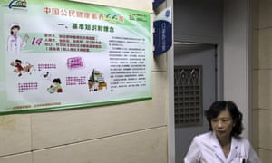 A hospital worker walks past a poster with information on rabies vaccine in Beijing, China.