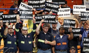A group of coal miners wave signs for Republican presidential candidate Donald Trump as they wait for a rally in Charleston, West Virginia on Thursday.