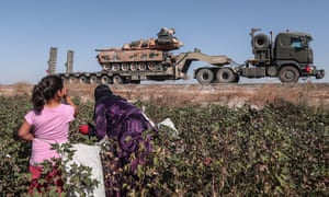 Agricultural workers watch Turkish military vehicles on the way to northern Syria.