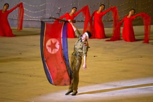 An actor raises the North Korean national flag during a segment depicting the founding of the country.