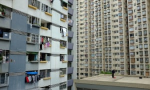 A cleaner is dwarfed by the buildings in Hong Kong