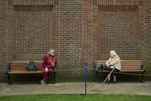 Two women observe social distancing measures as they speak to each other from adjacent park benches amidst the novel coronavirus COVID-19 pandemic, in the centre of York, northern England on March 19, 2020.