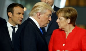 Donald Trump walks past French president Macron and German chancellor Merkel during a Nato summit. Trump withdrew the US from the Paris deal on Thursday.