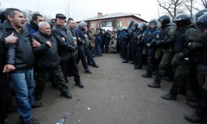 Demonstrators  in Novi Sanzhary, Ukraine, confront law enforcement officers as they protest the arrival of evacuees from Covid-19-hit China.