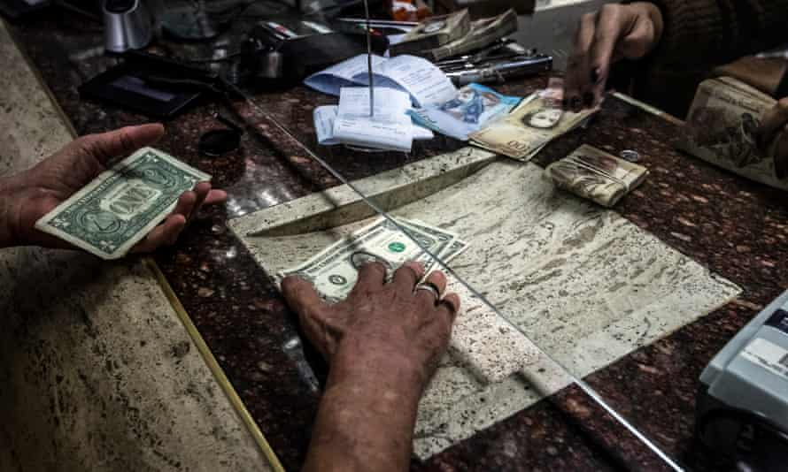A customer receives US dollars during a transaction at an Italcambio currency exchange house in Caracas.