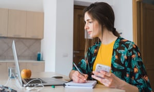 Young woman sitting at table at home using cell phone and laptop taking notes