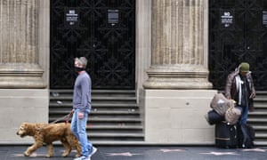 A man wearing a mask walks his dog past a homeless man along Hollywood Boulevard in Los Angeles.