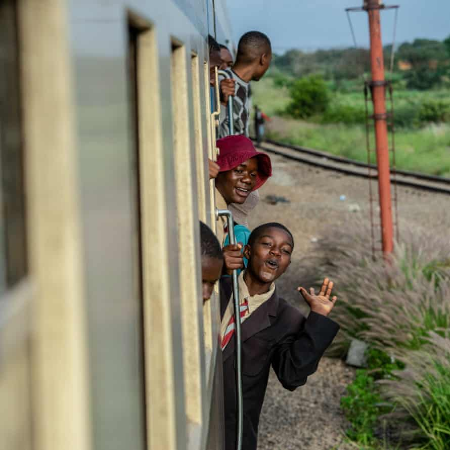 Passengers hang on the sides of the train