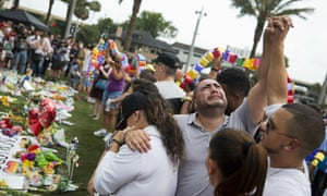 Jose Hernandez, center, joins hands with Victor Baez, right, as they mourn the loss of their friends Amanda Alvear and Mercedez Flores in the Pulse nightclub shooting.