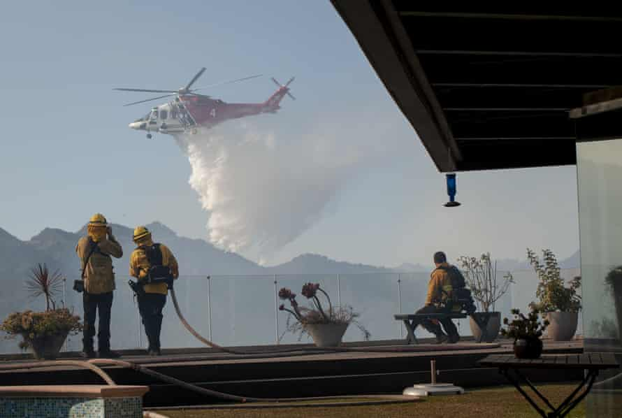 Firefighters watch from a home in the Pacific Palisades area as a helicopter drops water on a wildfire.