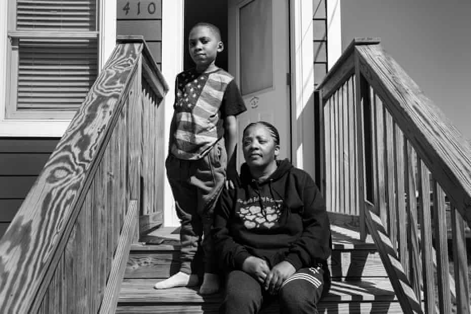 Kimberly White Smalls sits on her front stairs with her grandson Donovan E Smalls, nine, on Beach 43rd Street in the Edgemere neighborhood of Far Rockaway, Queens.