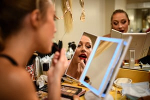 A dancer makes herself up in the wings.