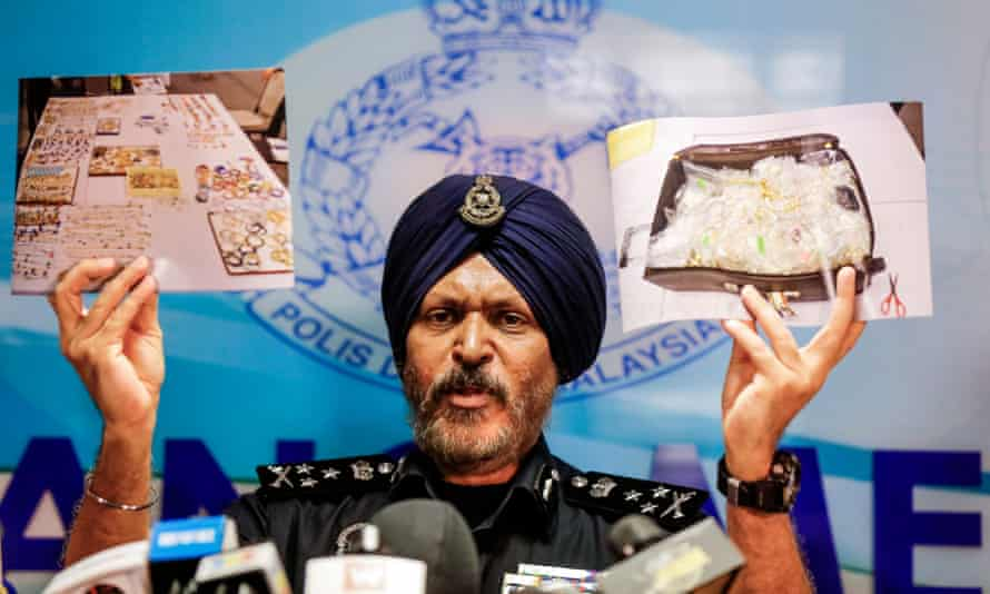 A Malaysian police director shows a photograph of items collected during a raid on Najib Razak's homes.