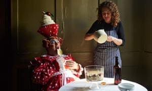 Rachel Roddy and her brother Ben, who is dressed as a pantomime dame, eat trifle at her table