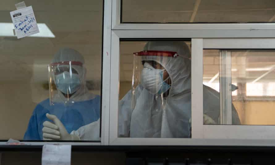 A doctor in a Covid-19 zone talks to staff through a window in the Pakistan Institute of Medical Sciences in Islamabad.