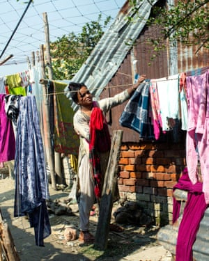 A woman hanging her clothes on the washing line in Rasulpur, Barishal, Bangladesh.