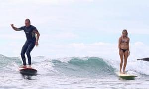 Tony Abbott surfs beside Ivy Thomas at Tea Tree Bay near Noosa