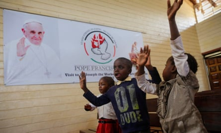 Kenyan children sing in front of a banner welcoming Pope Francis at a church in Nairobi.