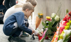 People lay flowers and candles outside the OEZ shopping centre the day after the shooting spree in Munich.