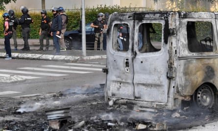 A burned out white van and police standing in the background.