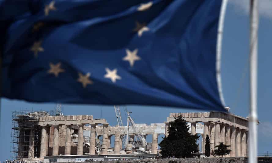 An EU flag waves above the ancient temple of Parthenon in Athens.