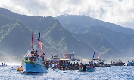 Spectators watch surfers compete at the Teahupo'o surf trials in Tahiti in August.