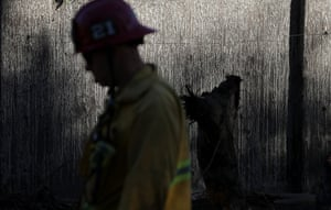 A firefighter walks by a mud-covered wall in front of a home destroyed by a mudslide in Montecito, California on 11 January. Twenty-one people died and hundreds of homes were destroyed or damaged