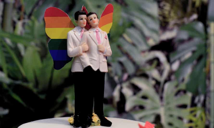 A rainbow wedding cake for a same-sex marriage, featuring two grooms