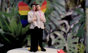 Two grooms with rainbow wings on a wedding cake