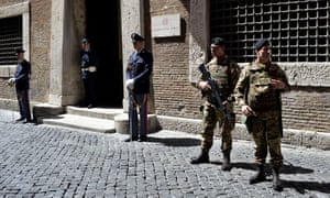 Police officers and soldiers stand guard outside the Italian national anti-mafia services HQ in Rome.
