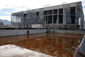 Translucent tapestries created by the Brazilian artist Adriana Varejao, fall from the exterior of the aquatics centre as a combination of mud, rainwater and dead insects have contributed to the rust colour of the water in a practice pool