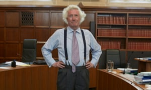 Jonathan Sumption, hands on hips, in an office full o red tomes