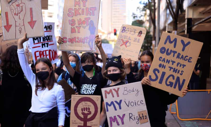 """Girls hold up placards at the """"March 4 Justice"""" rally in Sydney"""