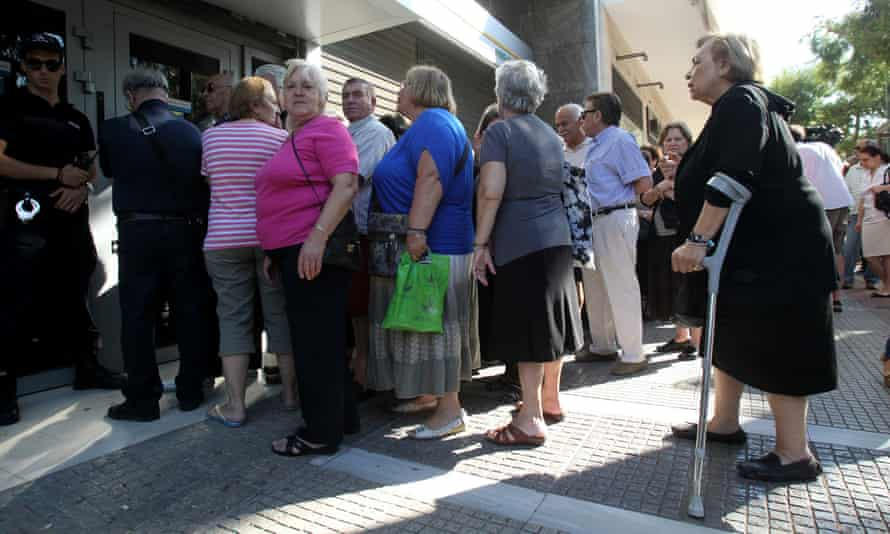 Greek pensioners without bank cards line up outside a bank in Athens.