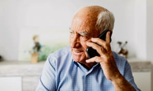 Happy retired man talking on the phone at home.