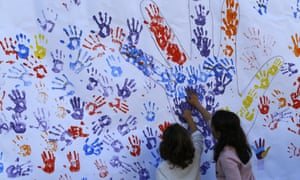 Children stamp their hands with paint on a paper wall during a Podemos party rally in Madrid.